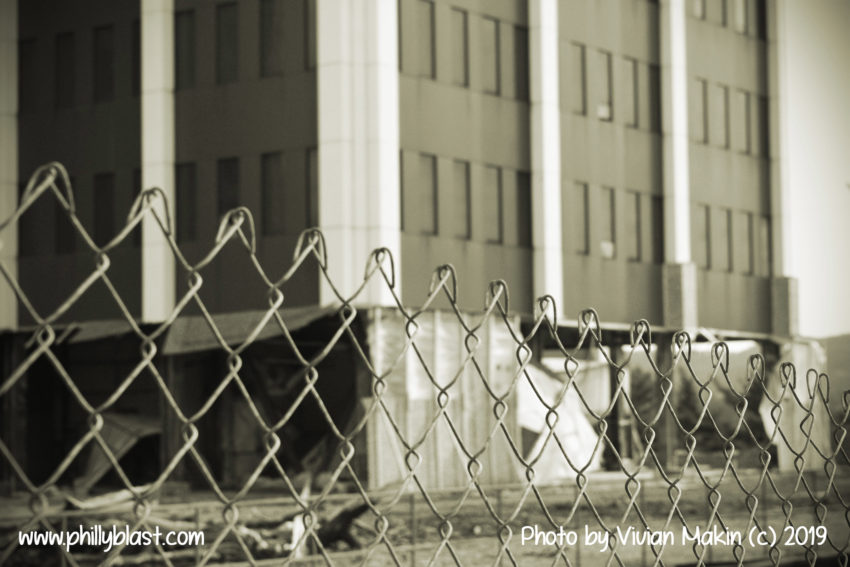 Sepia-toned view of bottom three floors of Martin Tower undergoing demolition as viewed through a chainlink fence
