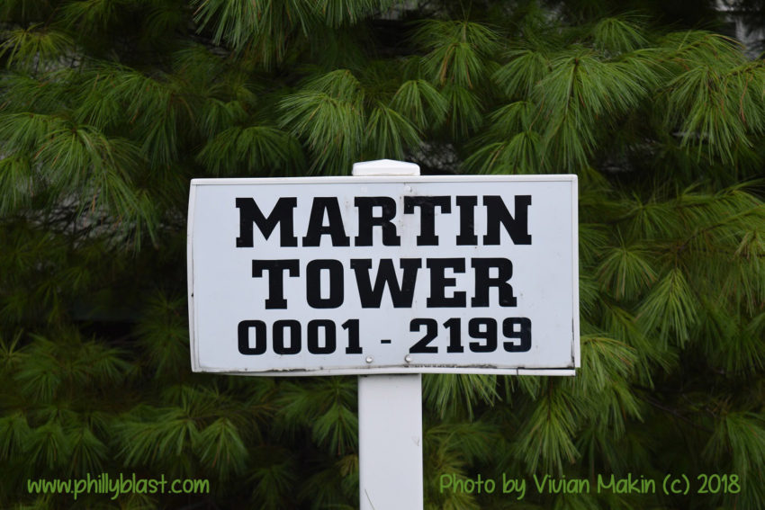 "A sign reading ""Martin Tower 0001 - 2199"" with greenery behind it"