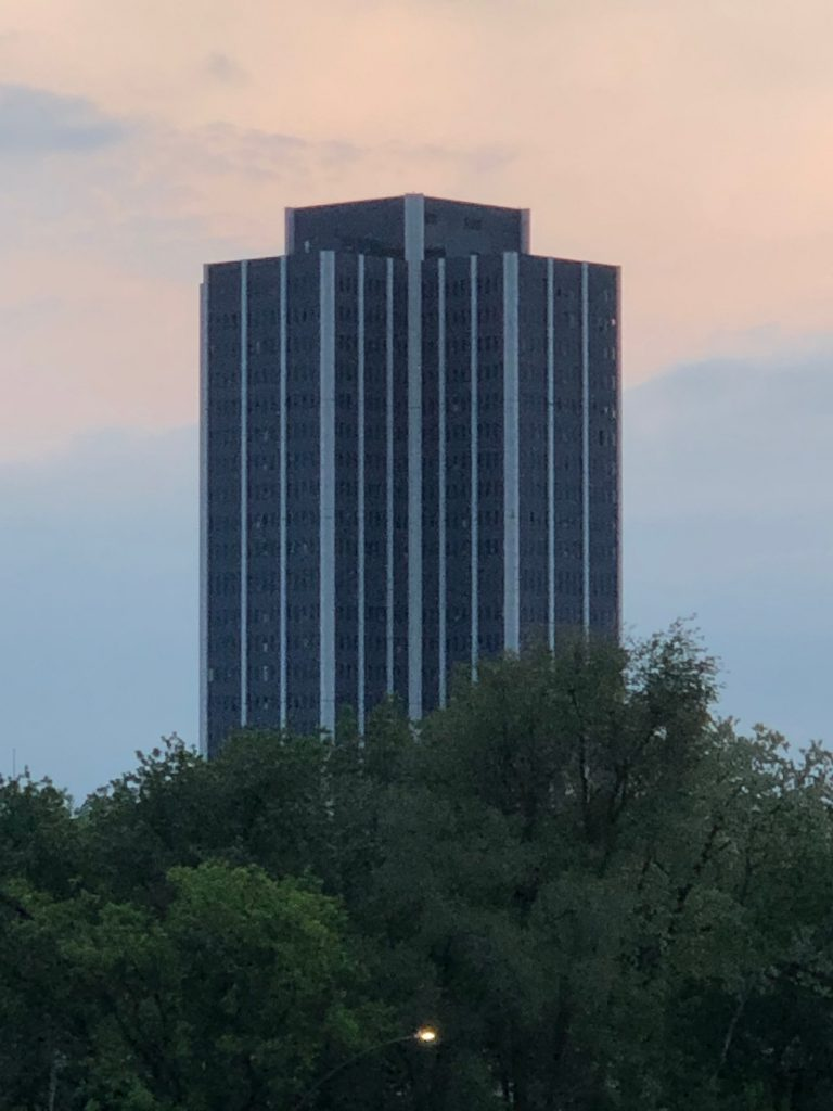 Grey and white skyscraper with trees at its base and the sun rising in the background