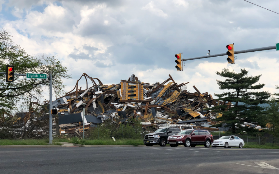 View of Martin Tower debris pile in the background with cars stopped at traffic light in the foreground