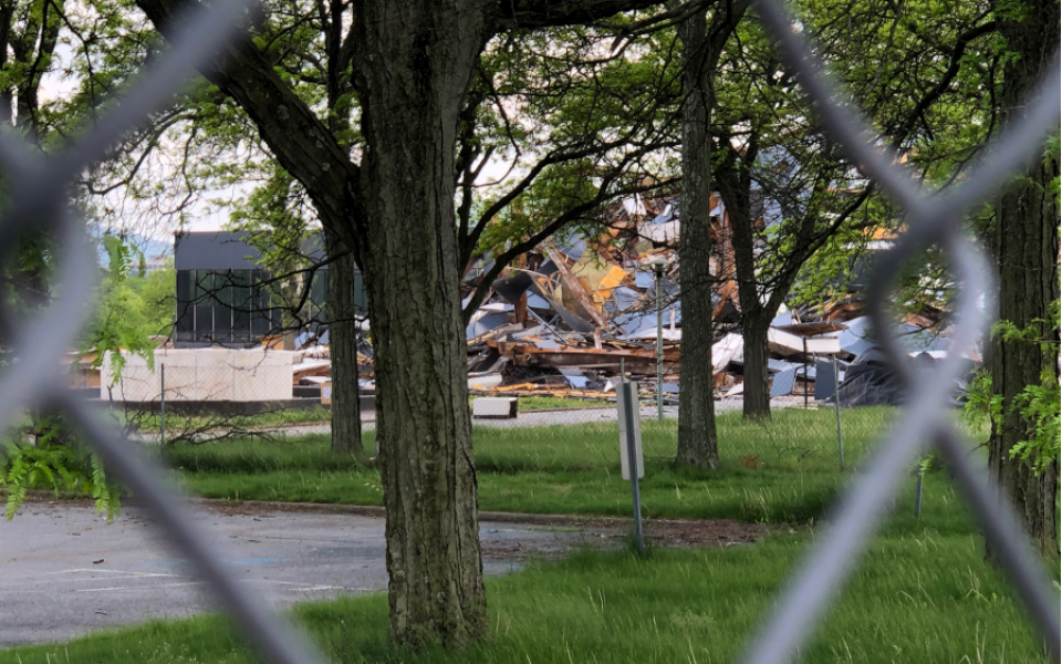Martin Tower debris pile viewed through chainlink fence with trees in foreground and annex connector still intact to the left side